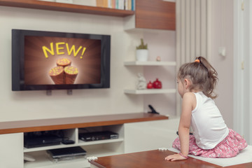 cute little girl watching advertisement on tv